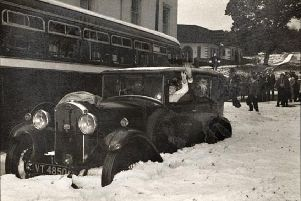 This vintage snap shows a car stranded in the snow.