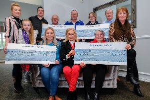 Saintfield Christmas Charity Ride organiser Joan Cunningham (seated centre) with, front row from left, Elizabeth Kane, Angelina Kane (Make a Wish, Never to be forgotten and Headway Charities. Joanne Smith (Cancer Focus) Valerie Morrison (PDSA) and Vi Patterson. Back row from left, Angelo Kane, Robin Patterson, Morris Hanna, Cherith Hanna and Michael Andrews.