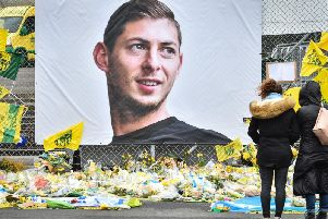 People look at yellow flowers displayed in front of the portrait of Argentinian forward Emiliano Sala at the Beaujoire stadium in Nantes (Picture by LOIC VENANCE/AFP/Getty Images)
