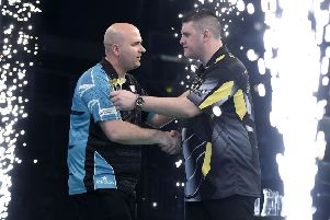 Rob Cross (left) shakes hands with beaten opponent Daryl Gurney at the end of their match in Belfast tonight. Picture courtesy Michael Cooper/PDC