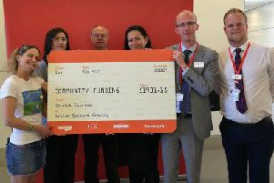 Maria Cook, Chair of Autism Support Crawley (left) takes delivery of a 'rail ticket cheque' from Gatwick Express managers