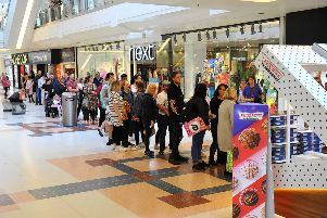 People stand in line for the opening of the new Krispy Kreme store in County Mall, Crawley