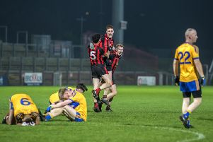 Red Hugh's Peader McGlinchey, Johnny Carlin and Stephen McMenamin celebrate their Ulster Junior Championship Final victory while distraught Limavady Wolfhounds players slump to the ground in Celtic Park on Saturday. DER4618GS035