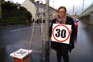 Sinn Fein Councillor Sharon Duddy pictured at the weekend on the Lonemoor Road as the signs were being erected.
