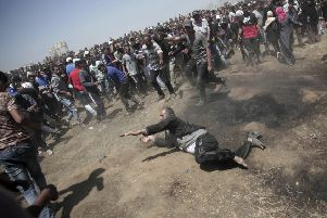 An elderly Palestinian man falls on the ground after being shot by Israeli troops during a deadly protest at the Gaza Strip's border with Israel, east of Khan Younis, Gaza Strip on May 14, 2018. Thousands of Palestinians were protesting near Gaza's border with Israel, as Israel celebrates the inauguration of a new U.S. Embassy in contested Jerusalem. (AP Photo/Adel Hana)