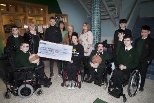 �1,000 RAISED BY ST. JOSEPH'S STUDENTS. . . . .Mrs. Martina McCarron, Principal and Mr. Emmet McGinty, PE teacher, pictured handing over a cheque for �1,000 to Sam McColgan, treasurer, North West Wolves Wheelchair Basketball Team for their CashForKids campaign, proceeds of a wheelchair basketball match between teachers and pupils at the Creggan school. Included are some of the pupils who played in the match including organisers Conor McRae, Jim O'Neill and Dylan Wade. At back centre are classroom assistants Maria Hribar, Annette McCallion and Paula Dillon. (Photo: Jim McCafferty Photography)