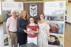 Niamh Reynolds presents vouchers to St. Anthony's principal Aine Fleming which she won at the  Lagan Camerata. Included is chair of the Board of Governors Damien Donaghy and Carol McLarnon, primary seven teacher and school musical director.