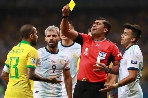 Referee Rody Zambrano books Dani Alves as Argentina's Sergio Aguero watches on. Picture courtesy of Getty Images