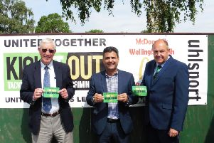 To launch the United Together campaign locally, Perry Akhtar (centre) provided a banner for Wellingborough Town alongside United Counties League director Jon Smith (right) and Doughboys president Laurie Owen