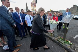 Sammy Devenny's daughter Anne places flowers at his memorial on William Street on Wednesday evening last. Mr Devenny died after he was attacked by members of the RUC, in his home, 50 years ago. DER2919GS-030