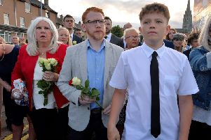 Christine Robson, daughter of the late Sammy Devenny , and some of his grandchildren, mark the 50th anniversary of his death, at his memorial on William Street on Wednesday evening last. Mr Devenny died after he was attacked by members of the RUC, in his home, 50 years ago. DER2919GS-029