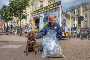 Trading Standards Officer Roger Cohen pictured with tobacco detection dog Yoyo and suspected illegal tobacco seized this morning SUS-190813-164451001