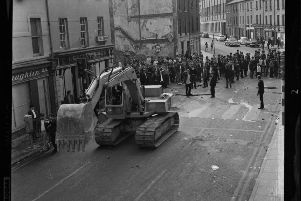 A digger is driven into William Street at the height of the July 12 riots.
