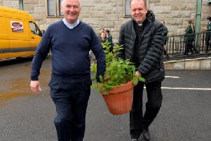 Fr Paul Fraser and Fr Joe Gormley carrying an Oak sapling for planting to commemorate the 60th anniversary of St Mary's Church Creggan. DER2219GS-026