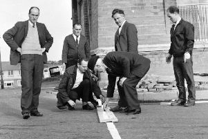 Paddy 'Bogside' Doherty, standing second from right, looks on as a white line replaces a barricade as the boundary marker for the Free Derry 'No Go' area.