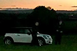 Police officers surround the vehicle after it is driven into a field in Co. Derry. (Photo: PSNI)