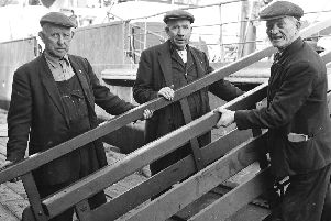 Derry dockers remove the gangway as the 'Scotch Boat' sets sail from the quayside. Taken in the 1960s.