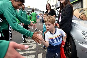 A young onlooker high fives visiting footballers during the opening ceremony parade in Coleraine for SuperCupNI 2018