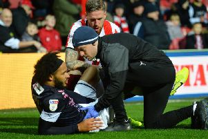 Izzy Brown gets treatment on his torn hamstring at Brentford yesterday