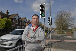 Matt Zalman at the traffic lights that he campaigned for outside St Thomas a Becket School in Eastbourne (Photo by Jon Rigby)