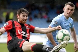 Howard Beverland hooks clear under pressure from Ballymena United's Shane McGinty during the weekend win for Crusaders. Pic by INPHO.
