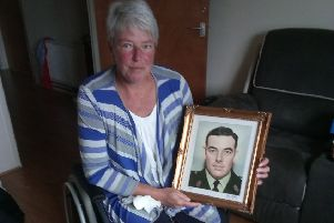 IRA bomb survivor Andrea Brown with a photo of her father Eric, who was murdered by the same group