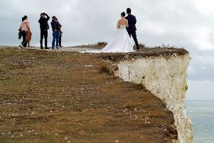 Newlyweds posing for photographs on the edge of Birling Gap cliffs. Photo by Peter Cripps
