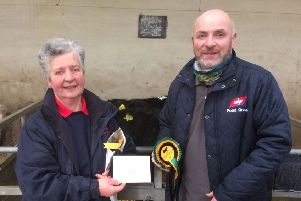 Robert White, Ballycastle, won first prize in the bull calf class at the NI Aberdeen Angus Club's dropped calf show and sale, held at Ballymena Mart. Adding her congratulations is club secretary Cathy O'Hara