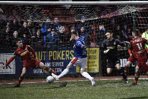 Mark Stafford tucks away the game's decisive goal in a victory for Linfield over Cliftonville that sent the defending Danske Bank Premiership champions back into top spot. Pic by Pacemaker.