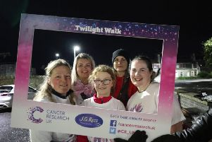 Some participants of this year's Twilight Walk make use of a photo prop at the event