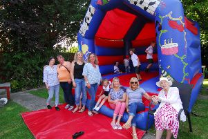 Residents, staff and friends enjoy time on the bouncy castle at the Ashdene summer fair.