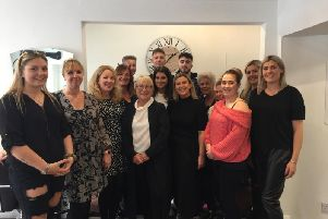 Staff and family celebrate 25 years of business at the salon.