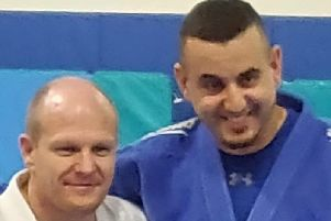 Rush Judo coach Salah Rabia, right, being presented with his black-belt by fellow Rush coach Laurie Rush.