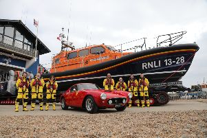 The red Ferrari pictured in front of the lifeboat it funded, alongside Hastings RNLI crew members. Photo by Kt Bruce. SUS-190423-122200001