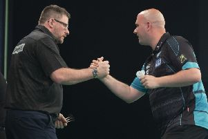 Rob Cross (right) shakes hands with James Wade at the end of their match. Picture courtesy Lawrence Lustig/PDC