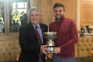 Rugby Golf Club captain, Camillus McCarron presents Dale Marson with the Championship trophy for the fifth time