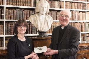 Tracey Braziel, Marketing Manager, at Ulster Carpets, presents a donation for Armagh Robinson Library to Dean of Armagh Gregory Dunstan.