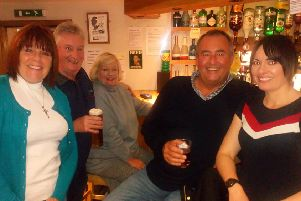 Wendy (left), Steve (second right) and Zara (right) enjoy a drink with a couple of locals