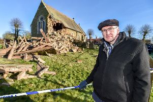 The Rev Charles Patrick  surveys the damage from behind the police line  at High Toynton church. Photo: John Aron