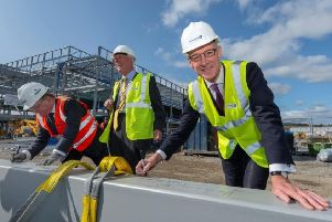 Provost of Aberdeenshire Bill Howatson, Deputy First Minister John Swinney and Derek Shewan, Chief Executive Officer of Robertson Construction sign the final beam before it was lifted into place