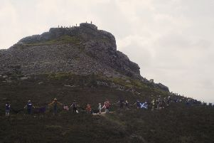 Walkers link hands to give Bennachie a bosie, with Kintore Pipe Band playing at the top of Mither Tap