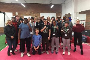 Babs Kandola (centre with black tracksuit and glasses) stands with members and others involved with Leamington Community Boxing Club at the club's new gym.