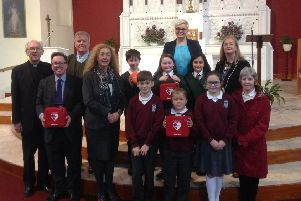 Larne Parish has been presented with three defibrillators by the Bravehearts NI charity. Pictured at the presentation are back row (l-r): Fr Aidan Kerr, Parish Priest; Tommy Lismore, governor, St Anthony's Primary School; Clare Caulfield, founder and director, Bravehearts NI; Bibiana McCavera, principal, St MacNissi's Primary School; Middle: Paul Fitzpatrick, Larne Parish Finance Committee; �ine Fleming, principal, St Anthony's Primary School; St MacNissi's pupils Eoin Fitzpatrick, Mya Frame, Angela Rose Jones-Castro. Front: St. Anthony's pupils Kian McAllister; Lee McAllister; Niamh Reynolds and Patricia McCullough, chair of the board of governors, St. MacNissi's Primary School.