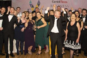 Some of the award winners at the Carrick Business Excellence Awards celebrate on the stage.'INCT11-19051BW