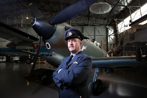 Nicholas Collett with a Spitfire fighter aeroplane at the South Australian Aviation Museum. Picture: Matt Turner.