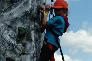 A young Aylesbury Scout tries her hand at the climbing wall during a previous scout camp