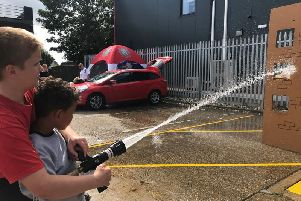 Trey Thomas, 6, of Rainham  in Essex, is shown how to do use a hosereel by Fire cadet Harry Barke,13.