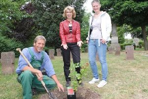 Mayor Franziska Schwarz (center) and plant manager Astrid Schelle (right) along with horticultural expert Peer Opitz planting the rose,
