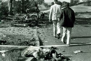 Personal belongings of the Miami showband members lie in the foreground as police officers examine the scene of the ambush of the band's minibus on the road between Banbridge and Newry in 1975.