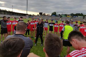 Derry manager Paddy Campbell talks to his players after Sunday's victory.